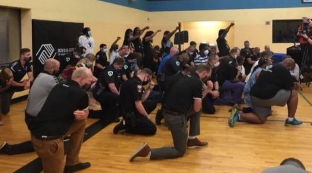 Police kneel, black power fist